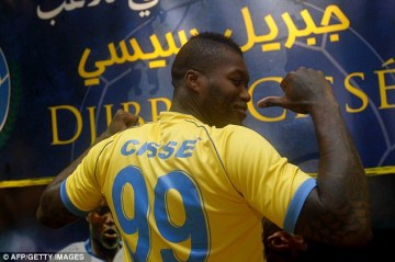 Shipped out | Djibril Cissé shows off his new Al-Gharafa shirt, after joining the Qatari club on loan. (Image | Daily Mail)
