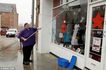 Big job | Gerald cleans shop front. (Image | Capital Bay)