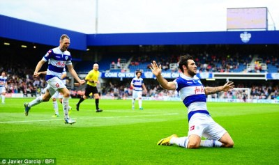 High flyer | Charlie Austin slides across the Loftus Road turf after scoring against Barnsley. (Image | Daily Mail)